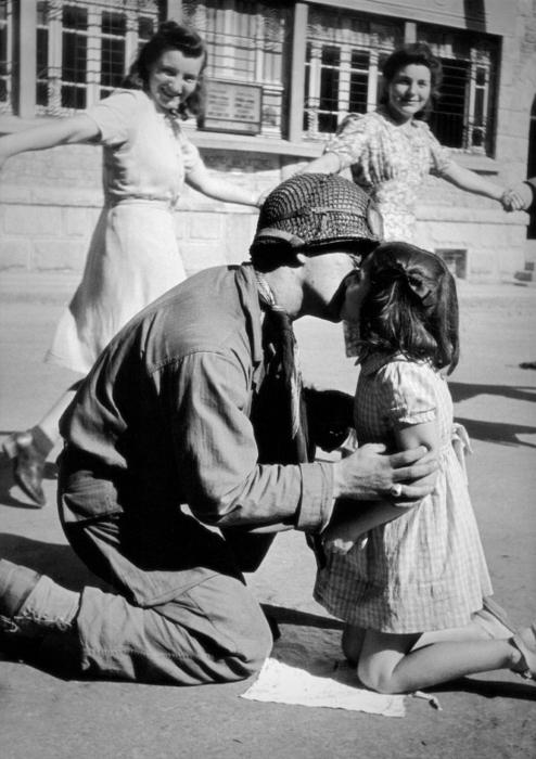"""Un soldato americano bacia una bambina italiana. Intorno a loro, delle giovani donne ballano.  Copyright image name: """"Kiss of liberation"""""""