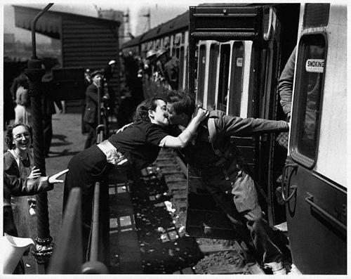 Una coppia di innamorati in stazione  si saluta mentre il treno sta per partire.